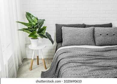 bedroom interior dekor bed in gray tones with flower on bedside table