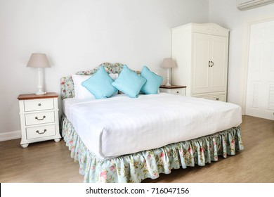 Bedroom interior design, Blue backrest pillows on white bed with floral bedspread next to white furnitures and desk lamps.