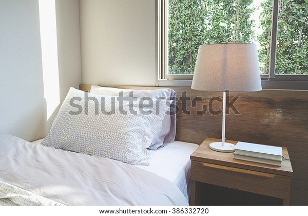 bedroom interior design with pillows on bed and decorative table lamp.