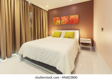 Bedroom interior design with red pictures on brown wall