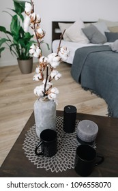 Bedroom interior details. Cotton twig, candles and cups on a coffee table