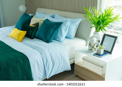 bedroom interior in gray green tones with comfortable cushions and green blanket.