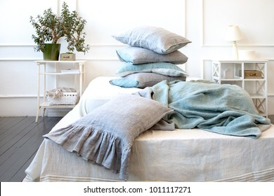 Bedroom interior with linen bedding, duvet covers, pillows.