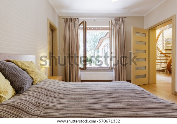 Bedroom interior with open window, marital bed and entry to staircase