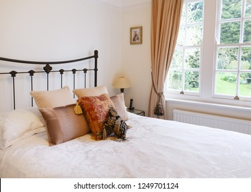 Bedroom interior in a traditional style English house with luxury soft furnishing