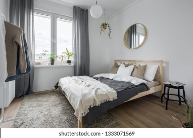 Bedroom interior with wooden bed, gray window curtains and mirror