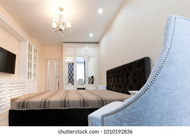 A bedroom in light colors with a dark bed and a soft chair with rivets in the foreground