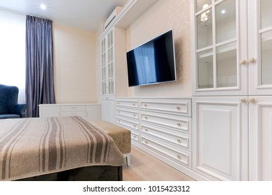 Bedroom in light colors with dark bed and blue curtains