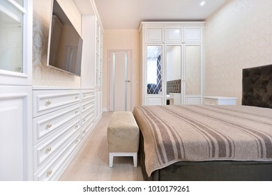 Bedroom in light colors with wooden furniture