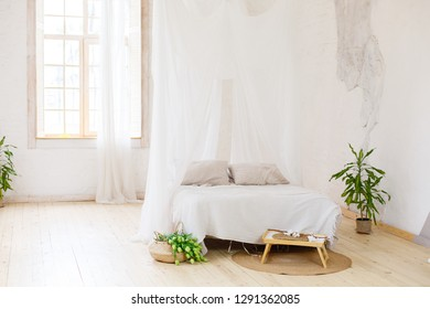 A bedroom in light scandinavian stile with light bed and white canopy. Comfortable bedroom. A combination of modern and old.
