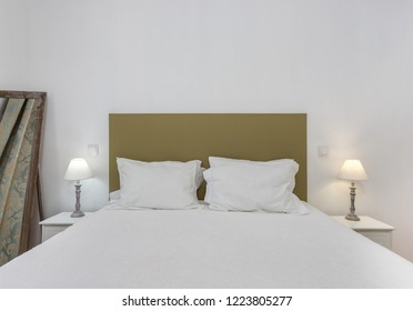 Bedroom in modern style with bed and pillows. Front view.