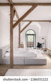 Bedroom in a modern style with white walls, wooden beams and a parquet with carpets. There is a gray bed with light linens, doors to a balcony, black armchair and a lamp, chests with a statuette.