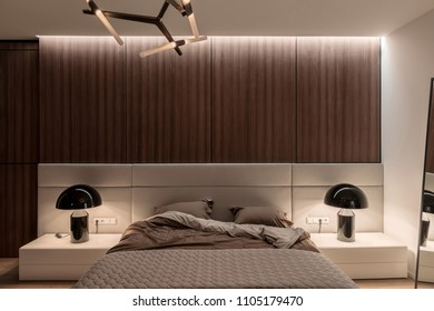 Bedroom in a modern style with white and wooden walls, parquet on a floor and luminous fancy lamps. There is a bed with a brown linens and a gray plaid, mirror, night stands. Horizontal.