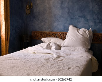 bedroom in the morning light with pillows threw askew.
