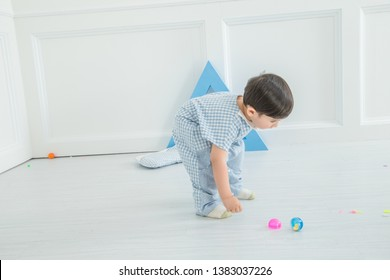 In the bedroom of the nursery, the boy in a lattice pajamas is playing with a blue triangular cube