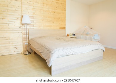 Bedroom in soft beige colors with blue decoration. Over the bed was a large frame with a white background where can be your tex.