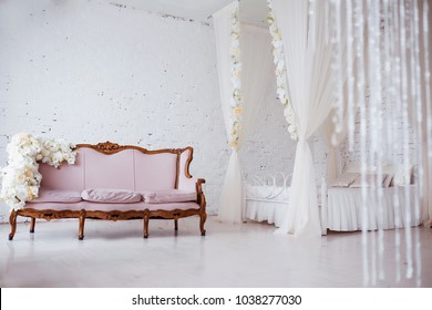 Bedroom in soft light colors. Big comfortable elegant double bed in white brick loft interior.