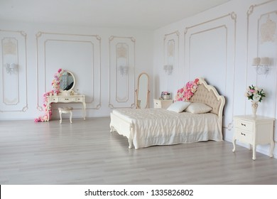 Bedroom in soft light colors. Big comfortable double bed decorated with flowers in elegant classic bedroom