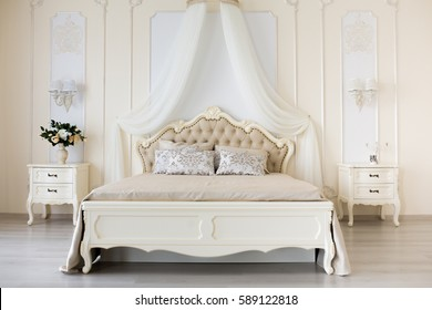 Bedroom in soft light colors. Big comfortable double bed in elegant classic interior