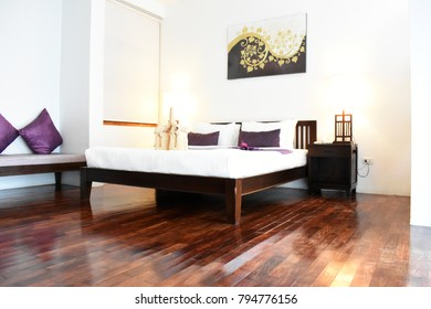bedroom in soft light colors. big comfortable double bed in elegant classic bedroom Colorful parquet flooring. Beautiful everything perfect