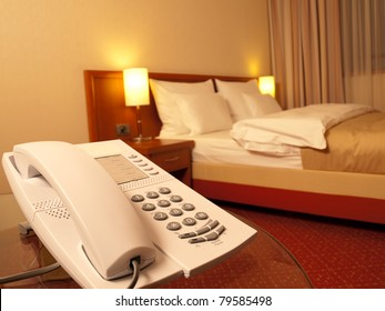 bedroom with telephone in front and bed in the background, focus on the telephone,for room service,communication themes