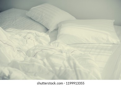bedroom with two pillows and crumpled bed sheet, after waking up in the morning