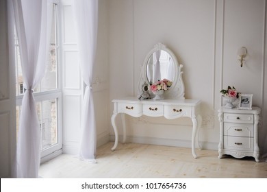 Bedroom in white colors, bed, sofa, dressing table with mirror. Interior. Glass doors. White tulle. Flowers on the table.