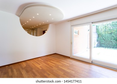 Bedroom with white walls and parquet. Arch with spotlights. Nobody inside