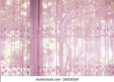 A bedroom windows dressed with striped curtain that lace drapery pattern with flower shape in an expensive luxury new home with the greens of the garden view.