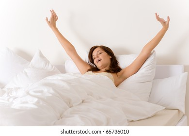 Bedroom - woman waking up and stretching in white bed