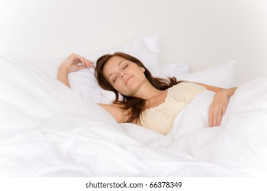 Bedroom - young woman sleeping and dreaming in white bed