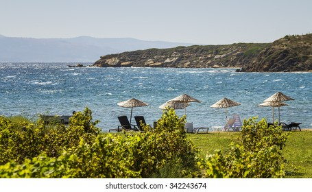 Beds and Straw Umbrellas On A Beach On A Windy Day By Grape Vines At Bozcaada, Canakkale, Turkey