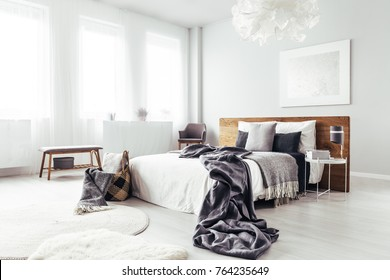 Bedsheets on king-size bed with wooden bedhead in bright bedroom with bench and basket
