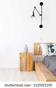 Bedsheets on a wooden king-size bed against a white wall in a spacious bedroom with lamp on a wall and a vase on a wooden bedside table. bed on a wooden base trunk