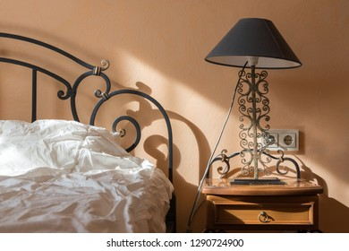 Bedside table with antique lamp by the bed