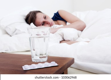 Bedside table with a glass of water, and a blister strip with pills and an awake, sick woman in the background