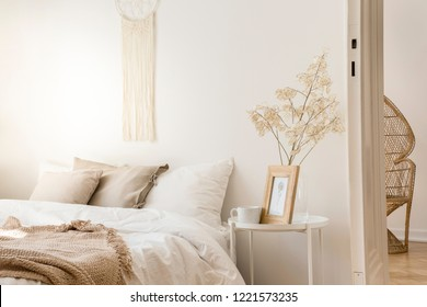 Bedside table with mug and framed picture next to comfortable king size bed with linen bedding and beige blanket, real photo
