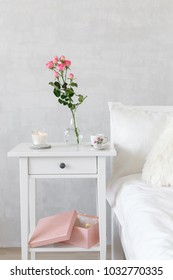 Bedside table, vase with rose flowers, lighted candle and cup of tea. Bed with white linen. Light female modern stylish and cozy bedroom. Bedroom interior.