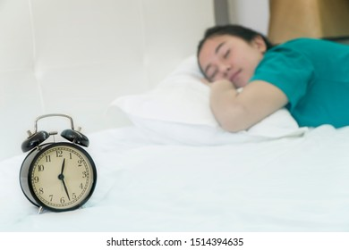 Bedtime sleep with alarm clock at noon or midnight time on bed in bedroom for world lazy day and healthy resting life balance, tried, not getting enough sleep, oversleep concept.
