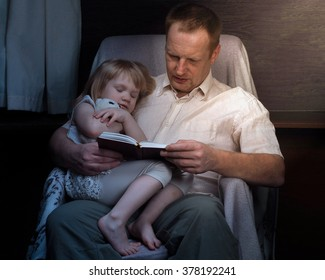 Bedtime Story. Dad daughter read a book. My daughter hugged the toy and falls asleep. Light from a lamp in a dark room. Family night
