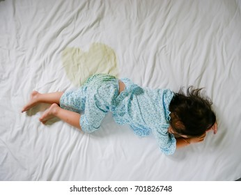 Bedwetting ,Child pee on a mattress,Little girl feet and pee in bed sheet,Child development concept ,selected focus at wet on the bed
