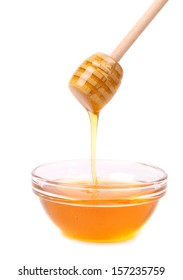 Bee honey with wooden dipper. Isolated on a white background