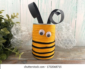 Bee made of wool yarn and cans, on a wooden background, children's creativity,
