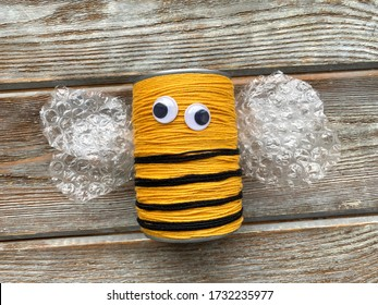 A bee made of yarn and a tin can without a mustache, children's creativity.