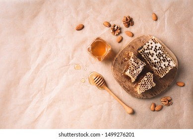 Bee pollen granules, honey jar with wooden dropper, honeycomb and almond nuts on craft paper backdrop. Copy space. Top view. Autumn harvest concept.