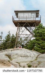 Beech Mountain, Acadia National Park, Maine, USA - September 20, 2018: Hikers relax at base of closed fire lookout tower at summit of Beech Mountain in Acadia National Park