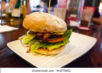 Beef and bacon burger with ice burg lettuce, tomato, cucumber and onion