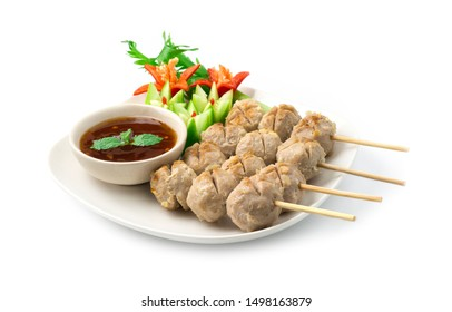Beef Ball Grilled in bamboo sticks inside dish with dipping sauce decorate with chili peppers,cucumber and vegetable Thai food appetizer dish style side view