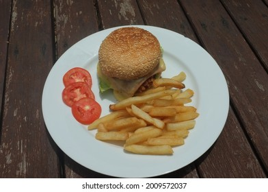 Beef  Berger cheese with French Fries and tomato .