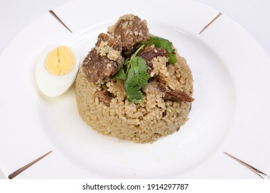 Beef Biryani Tehari cooked in mustered oil with boiled egg coriander leaf garnish on white plate over white background - Shutterstock ID 1914297787